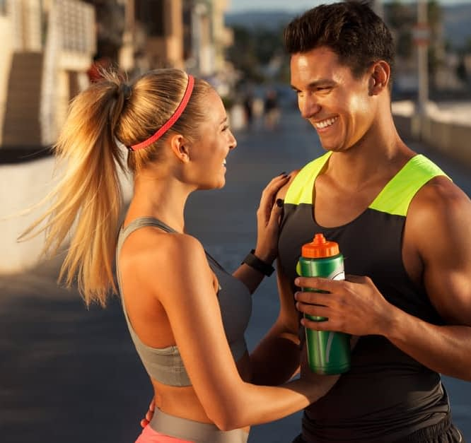 couple looking at each other wearing workout outfits